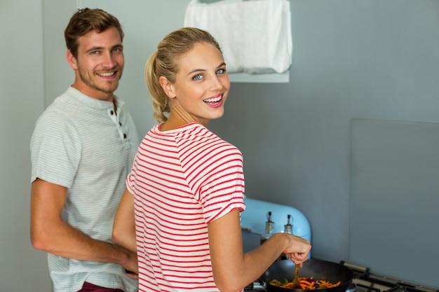Retrato de jovem casal cozinhar comida em casa