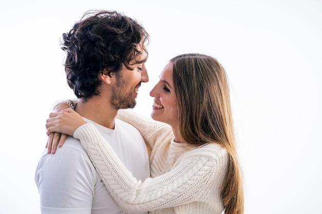 Retrato de jovem casal de estudantes isolados sobre fundo branco, sorrindo um para o outro