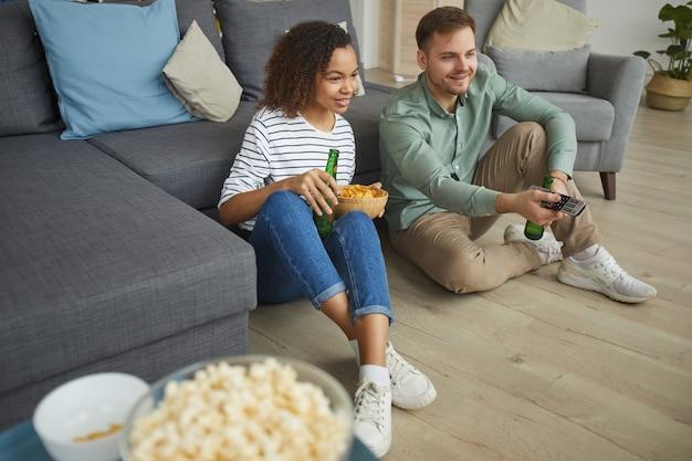 Retrato de jovem casal de raça mista assistindo tv em casa e bebendo cerveja enquanto está sentado no chão de um apartamento aconchegante
