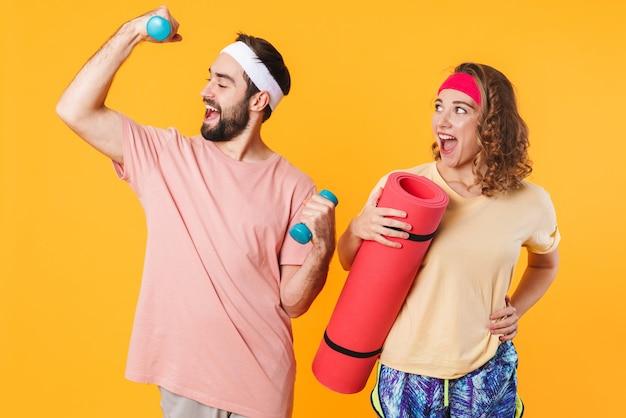 Retrato de jovem casal feliz atlético usando bandanas segurando halteres e um tapete de fitness isolado sobre a parede amarela