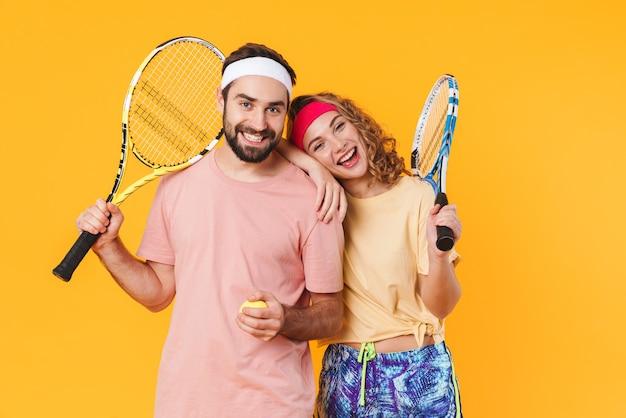 Retrato de jovem casal feliz atlético usando bandanas, segurando raquetes, enquanto joga tênis juntos, isolado sobre a parede amarela
