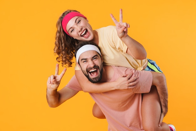 Retrato de jovem casal feliz atlético usando bandanas, sorrindo enquanto cavalgava nas costas, isolado sobre a parede amarela