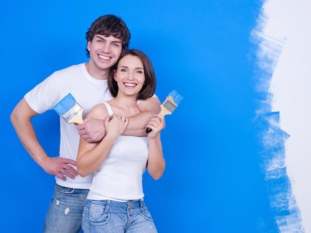 Retrato de jovem casal feliz e sorridente com pincéis