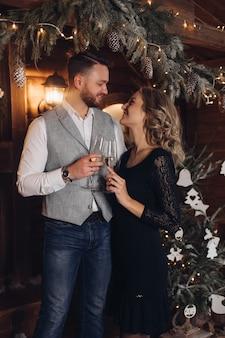 Retrato de jovem casal feliz em trajes elegantes, sorrindo cara a cara com duas taças de champanhe