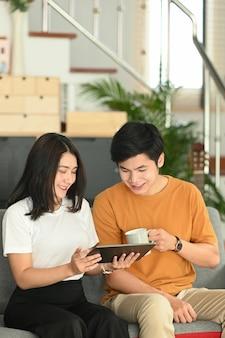 Retrato de jovem casal feliz usando tablet navegando na internet no sofá em casa