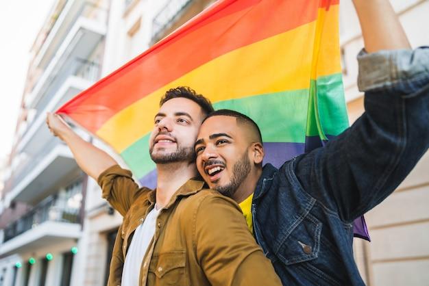 Retrato de jovem casal gay se abraçando e mostrando seu amor com a bandeira do arco-íris na rua