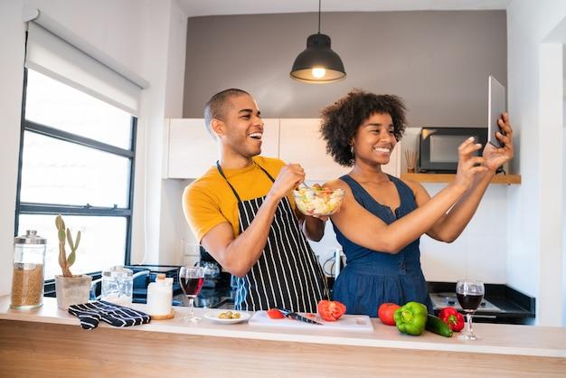 Retrato de jovem casal latino cozinhando juntos e tirando uma selfie com tablet digital na cozinha de casa
