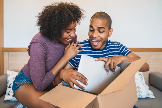 Retrato de jovem casal latino feliz abrindo um pacote com um laptop dentro, em casa. conceito de entrega, transporte e serviço postal.