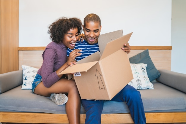 Retrato de jovem casal latino feliz abrindo um pacote em casa. conceito de entrega, transporte e serviço postal.