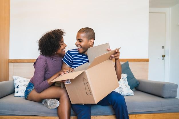 Retrato de jovem casal latino feliz abrindo um pacote em casa