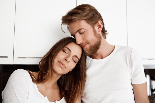 Retrato de jovem casal lindo sorrindo com os olhos fechados.