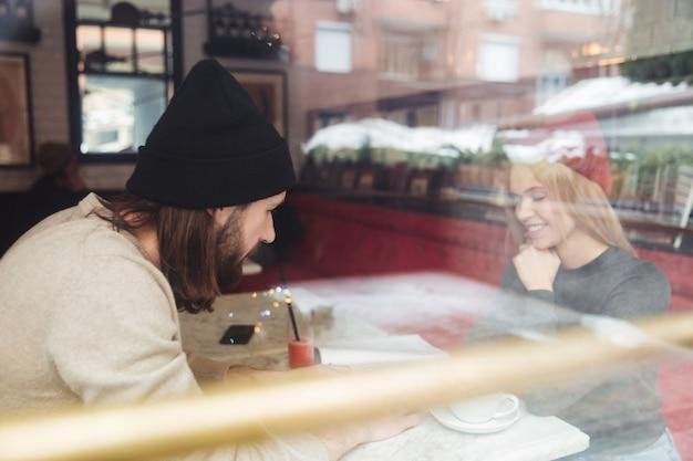 Retrato de jovem casal no café por trás do vidro