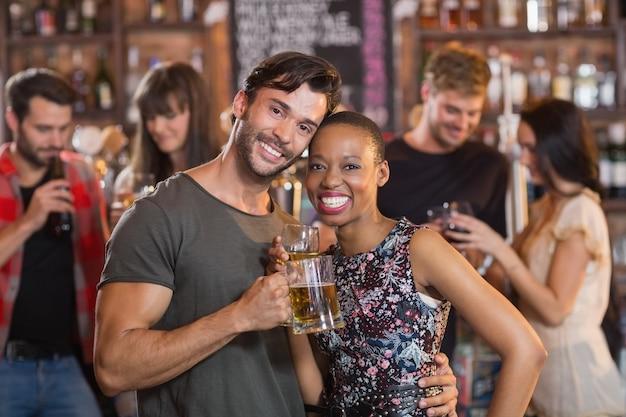 Retrato de jovem casal se abraçando, segurando canecas de cerveja