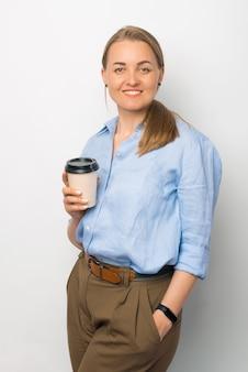 Retrato de jovem casual segurando uma xícara de café para levar e olhando para a câmera
