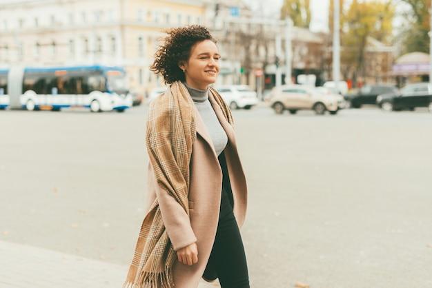 Retrato de jovem casual vestindo um belo casaco e andando na rua da cidade