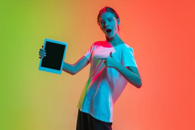 Retrato de jovem caucasiana em gradiente verde-laranja em luz de néon