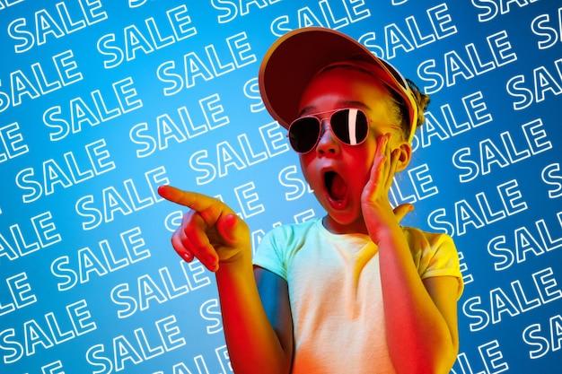 Retrato de jovem caucasiana em óculos de sol sobre fundo azul com letras de néon. conceito de vendas, sexta-feira negra, cyber segunda-feira, finanças, negócios. lojas online e contas de pagamentos.