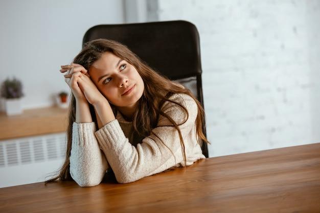 Retrato de jovem caucasiana em roupas casuais parece sonhador, fofo e feliz. olhando para cima e pensando, sentado dentro de casa à mesa de madeira. conceito de futuro, alvo, sonhos, visualização.