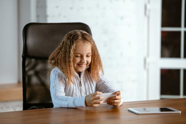 Retrato de jovem caucasiana parece sonhador, fofo e feliz. olhando para cima, sentado dentro de casa à mesa de madeira com tablet e smartphone. conceito de futuro, alvo, sonho de comprar, visualização.