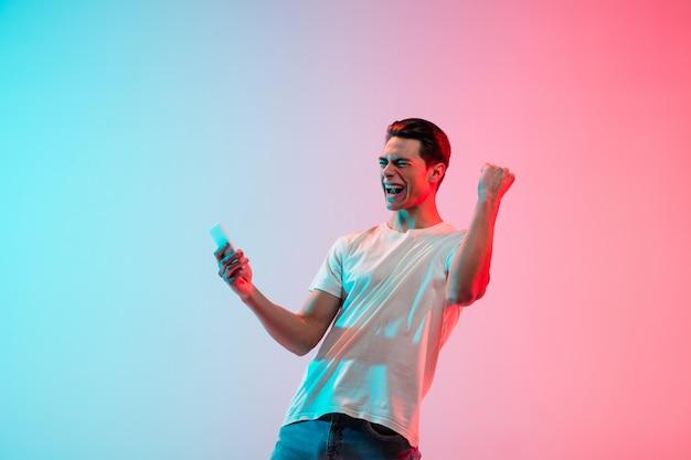Retrato de jovem caucasiano em fundo gradiente de estúdio azul-rosa em luz de néon