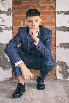 Retrato de jovem caucasiano em um elegante terno de negócios no fundo da parede de tijolo marrom, tonificado