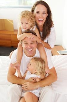 Retrato, de, jovem, caucasiano, família, sentar-se cama, casa, e, rir