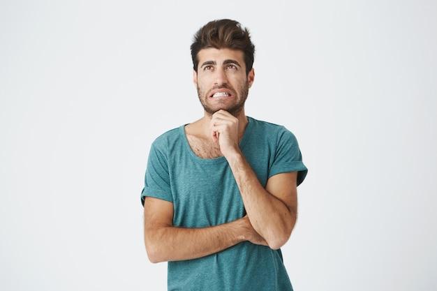 Retrato de jovem caucasiano infeliz na camiseta azul, com bom penteado e barba, fazendo expressão extremamente assustada pensando em pular a palestra do professor irritado.