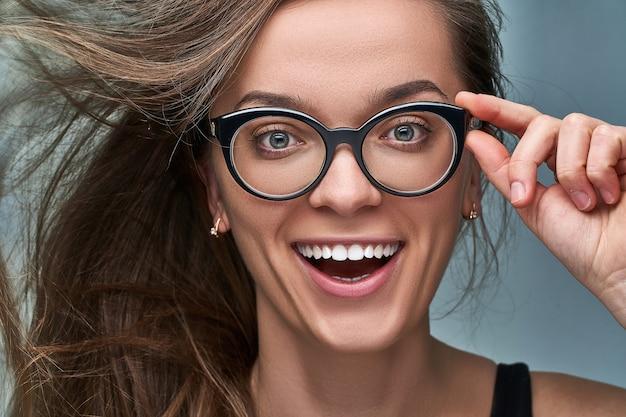 Retrato de jovem caucasiano morena feliz fêmea com expressão de rosto chocado animado surpreso alegre surpreso em óculos de armação preta com a boca aberta em surpresa. uau e omg