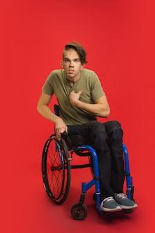 Retrato de jovem caucasiano no estúdio vermelho. conceito de emoções humanas