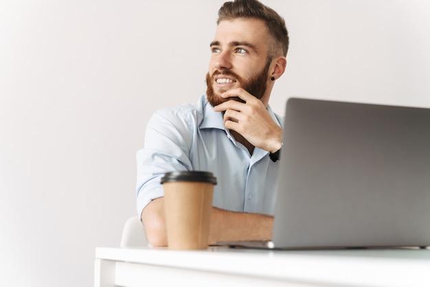 Retrato de jovem caucasiano vestindo uma camisa, trabalhando no laptop enquanto está sentado à mesa na sala branca