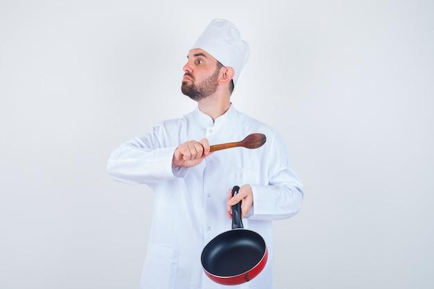Retrato de jovem chef masculino ameaçando com frigideira e colher de pau em uniforme branco e olhando a vista frontal nervosa