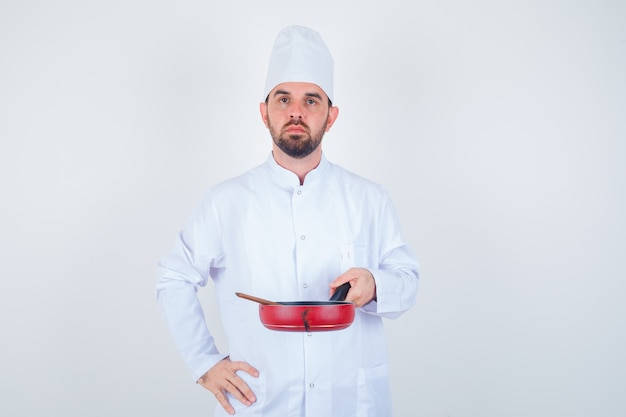 Retrato de jovem chef segurando uma frigideira com uma colher de pau em uniforme branco e olhando sério.