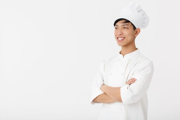 Retrato de jovem chinês com uniforme branco de cozinheiro e chapéu de chef, sorrindo para a câmera em pé, isolado sobre uma parede branca