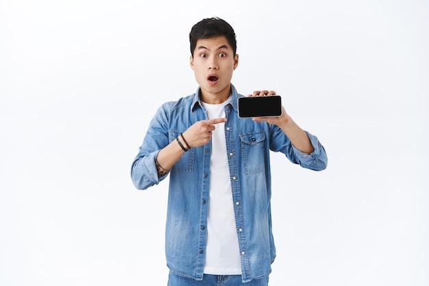 Retrato de jovem chocado e sem palavras mostrando o vídeo na tela do smartphone, segure o telefone celular horizontalmente, aponte para a tela e olhe para a câmera atônita