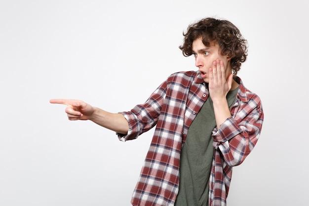 Retrato de jovem chocado em roupas casuais, colocando a mão na bochecha, apontando o dedo indicador isolado no fundo branco em estúdio. conceito de estilo de vida de emoções sinceras de pessoas. simule o espaço da cópia.