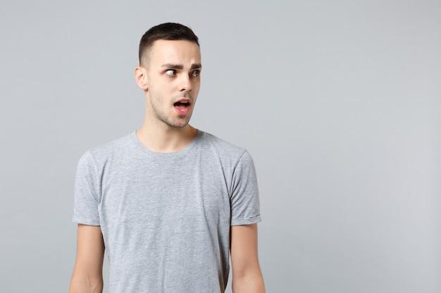 Retrato de jovem chocado em roupas casuais em pé, olhando para o lado, de boca aberta