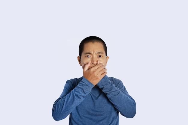 Retrato de jovem cobrindo a boca com a mão isolada de fundo.