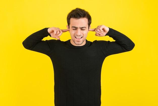 Retrato de jovem cobrindo as orelhas na parede amarela