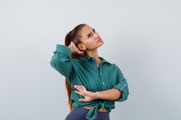 Retrato de jovem com a mão atrás da cabeça, olhando para cima com uma camisa verde e olhando pensativamente para a frente