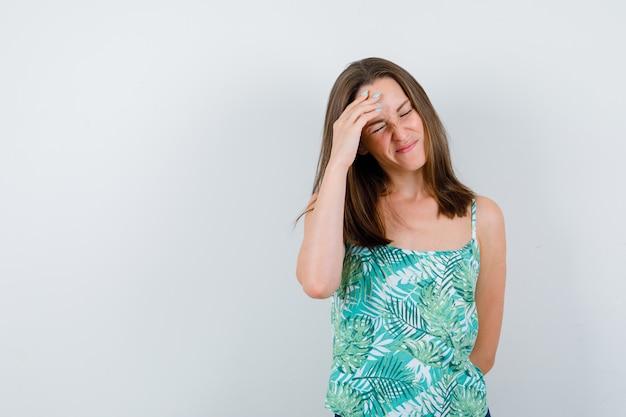 Retrato de jovem com a mão na testa na blusa e parecendo exausto com vista frontal