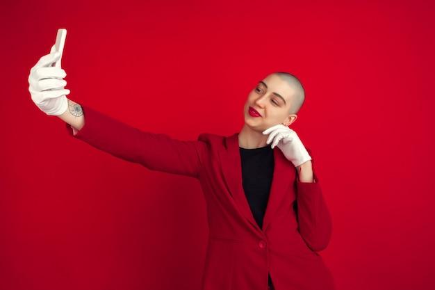 Retrato de jovem com aparência esquisita na parede vermelha