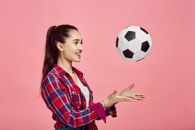 Retrato de jovem com bola de futebol, parede rosa. expressão facial, poses de pessoa feminina em estúdio, conceito de gênero, ocupação ou hobby
