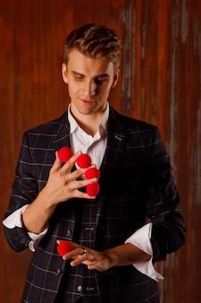 Retrato de jovem com bolas mágicas vermelhas. cara bonito mostra truques com bolas. mãos inteligentes de mágico