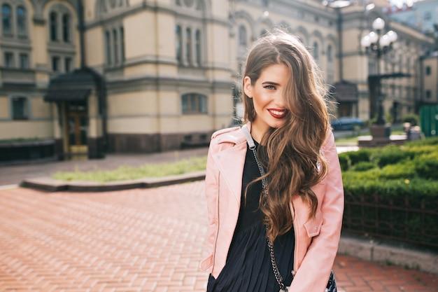 Retrato de jovem com cabelo longo cacheado e lábios vermelhos ela usa um vestido preto, jaqueta rosa. o cabelo cobre metade de seu rosto e ela está sorrindo.