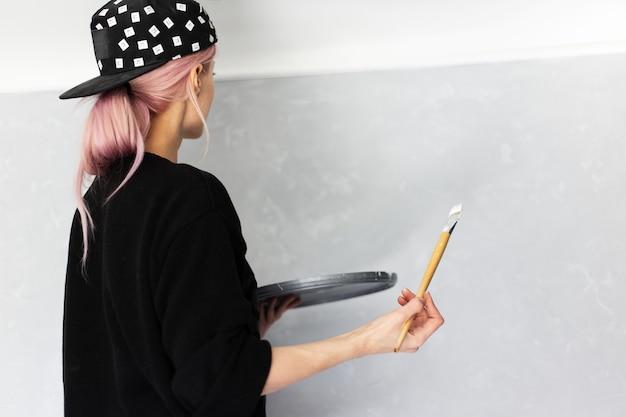 Retrato de jovem com cabelo rosa, pintura de parede com pincel e cor branca, no apartamento.