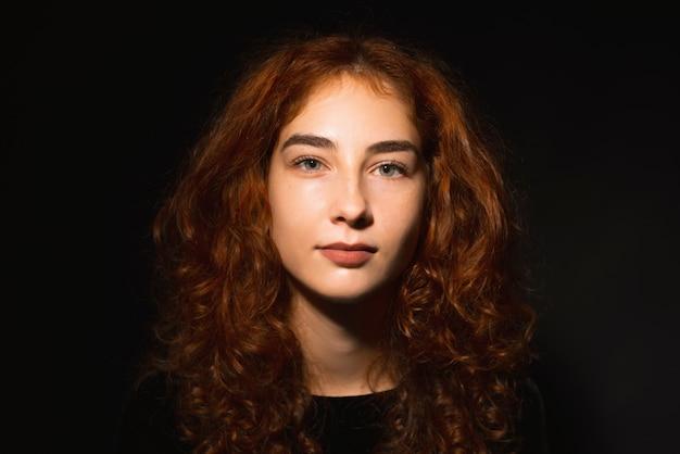 Retrato de jovem, com cabelo ruivo e encaracolado, sobre fundo escuro isoalted