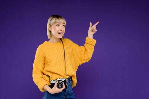 Retrato de jovem com câmera sobre parede roxa