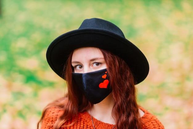 Retrato de jovem com camisola de malha vermelha, chapéu com uma máscara médica elegante preta no parque outono amarelo. moda, estilo de vida, quarentena, coronavírus.