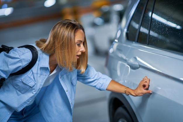 Retrato de jovem com carro riscado no estacionamento subterrâneo