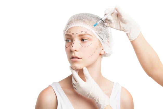 Retrato de jovem com chapéu de médico sendo injetado com uma seringa no rosto.